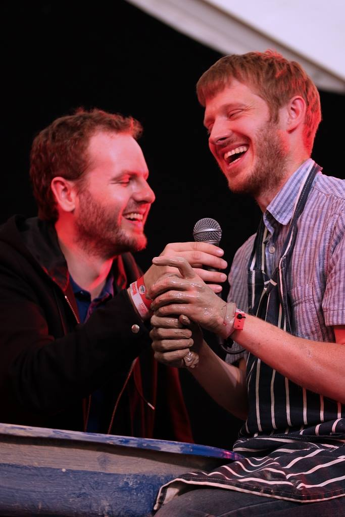 Photo of Sean and David laughing, Sean holding microphone while David does pottery
